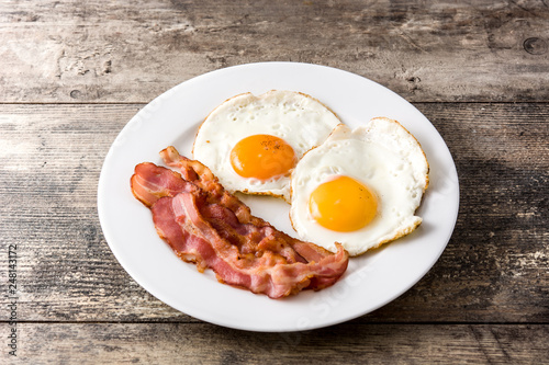 Fried eggs and bacon for breakfast on wooden table Wallpaper Mural