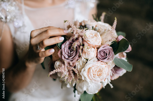 The bride holds a beautiful wedding bouquet of pink and white flowers in her han Canvas Print