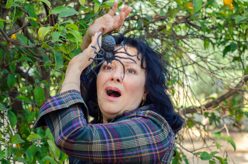 Fotografía  Woman meets a huge spider among green leaves of a tree