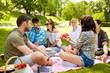 canvas print picture - friendship, leisure and summer concept - group of happy friends eating watermelon at picnic in park