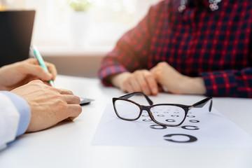Obraz na Szkleeye health - black glasses on eyesight test chart in optician office