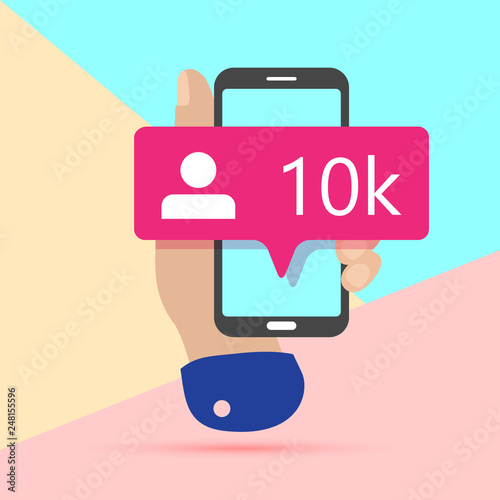 Fotografija  modern minimal hand holding mobile phone with new pink ten chiliad like followers social media iconon screen with shadow on pastel colored blue and background