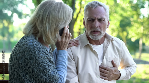 Photo Old couple sitting on bench, man suffering arrhythmia, wife calling emergency