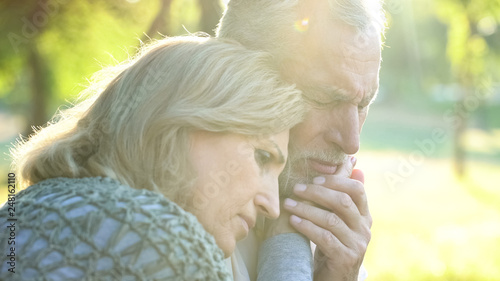 Fotografía  Sad senior wife embracing crying husband, relative loss, grief and sorrow
