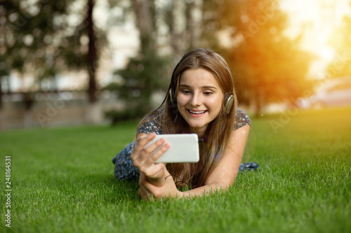 Woman looking wireless to a music video on a smartphone with