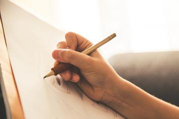 Pogled izbliza na mladu ruku koja crta na bijelom listu. Kid drži crnu drvenu olovku i kod kuće crta nešto na toplom narančastom svjetlu. Djeca koja pišu na papiru. Tinejdžerka crta od ruke mangu.