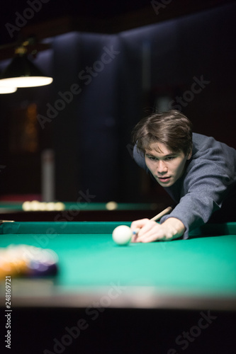 Photo Entertainment concept. A young man playing billiard