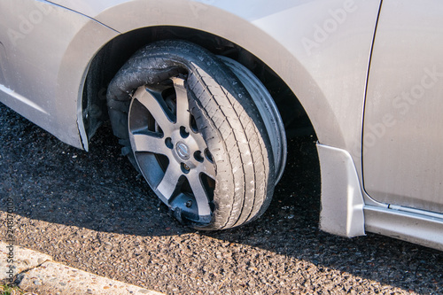 Fotografia, Obraz  Car tire that has a blowout with rim and car damage