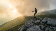 Young Hiker Man With Backpack And Walking Poles, Standing On Peak Of A Mountain Looking At Sunset In Cloudy Sky. Green Field And Rocks. Abruzzo, Italy.