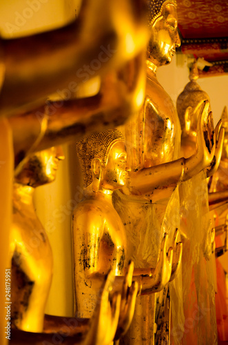 Traditional yellow gold statue of buddha meditating and praying in the royal palace temple for mind body soul spirit wellness and zen calmness