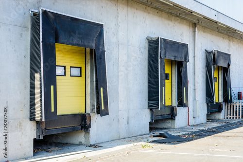 Fotografia Three truck loading docks with rubber seals in the concrete wall of a warehouse in the suburbs of Paris, France, with a closed yellow roller shutter door