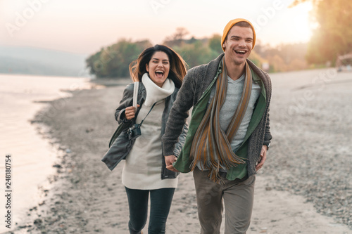 Fotografija  Cheerful young couple holding hands and running at the beach