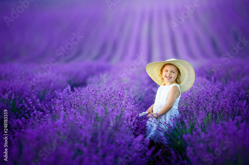 Poster Prune Cute young girl walking on a lavender field in white dress and hat on her head. Cute child face and nice hair with lavender bouquet