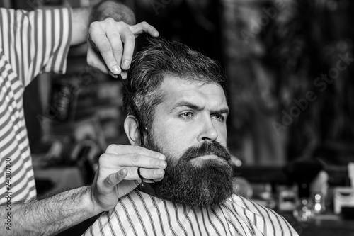 Foto op Plexiglas China Barber man serving client at barber shop. Vintage barbershop, shaving. Brutal bearded guy viziting hairstylist in barber shop. Making haircut look perfect. Hairdresser, hair salon. Black and white