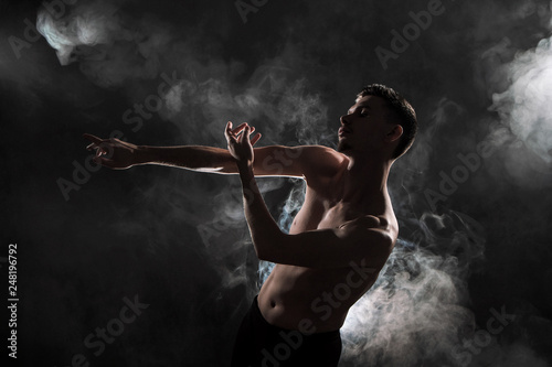 Fototapeta A young male ballet dancer with black leggings and a naked torso performs dance moves against a gray grunge background, with a light of lights and smoke