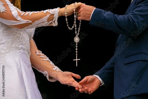 Fotografija  Mãos de uma mulher e um homem, noivos, segurando um terço com crucifixo em fundo