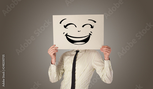 Fotografie, Obraz  Casual person holding a paper in front of his face with drawn emoticon face