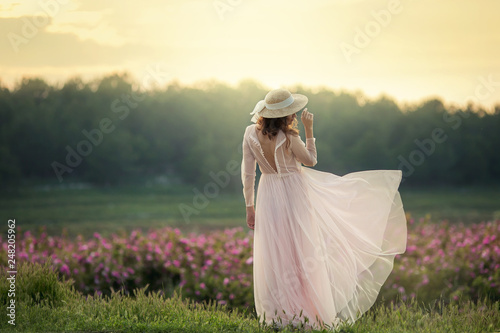 Fotografia, Obraz  Girl in a hat and a beige dress look at flower field.
