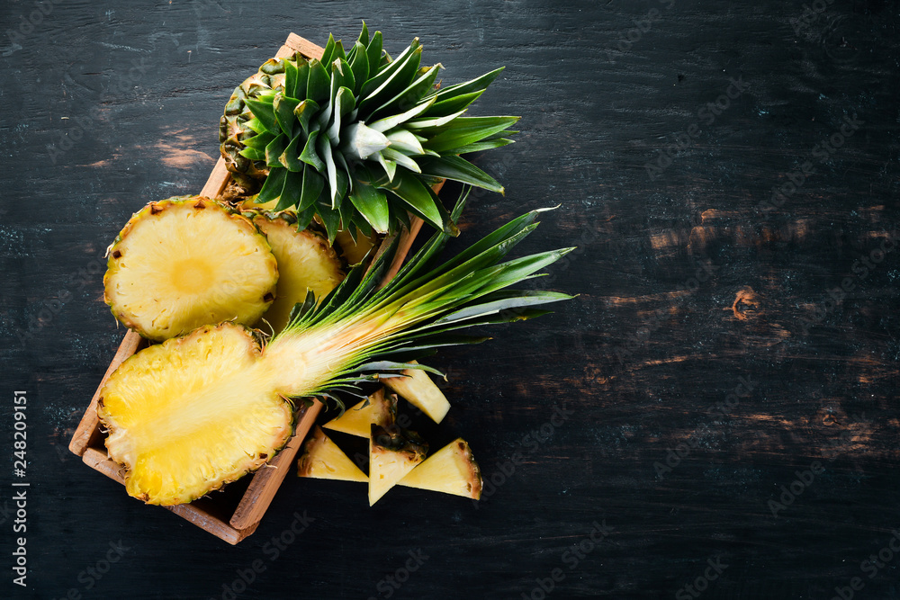 Fototapeta Pineapple. Sliced pineapple on a wooden background. Top view. Free copy space.