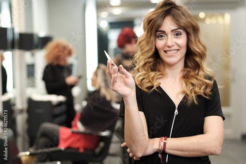 Valokuvatapetti Una chica joven peluquera en una peluquería donde se está trabajando