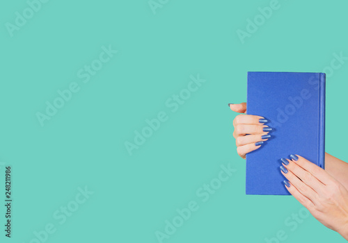Fotografie, Obraz  Closeup view of two female hands holding blue paper book isolated on green background with copyspace