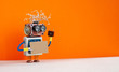 canvas print picture - Funny robot with a cardboard card mockup. Creative design robotic toy holding a blank and empty paper poster, orange wall background. copy space for text and design elements