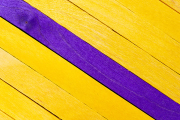 Yellow diagonal colored wooden background with purple stripe