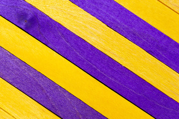 Yellow diagonal colored wooden background with purple stripes