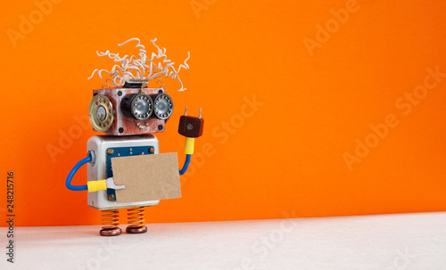 Obraz Funny robot with a cardboard card mockup. Creative design robotic toy holding a blank and empty paper poster, orange wall background. copy space for text and design elements - fototapety do salonu