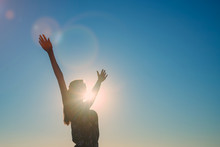 Silhouette Of A Girl With Arms Wide Apart, Blue Sky Background, Bright Sun And Rays
