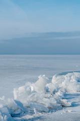 broken ice on a frozen lake against a blue sky