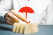 canvas print picture - Boss holding a red umbrella and defending his team with a gesture of protection. Life insurance. Customer care, care for employees. Security and safety in a business team. Selective focus