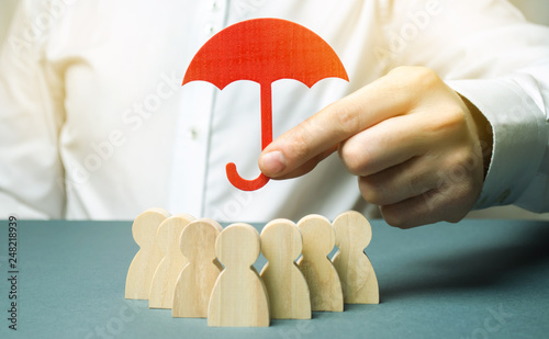 Fototapeta Boss holding a red umbrella and defending his team with a gesture of protection. Life insurance. Customer care, care for employees. Security and safety in a business team. Selective focus obraz
