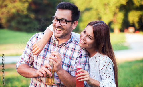 Stampa su Tela  Smiling couple having fun in the park. Love, dating, romance