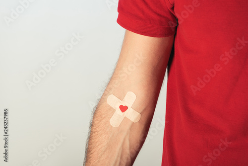 Photo  Partial view of patient in red t-shirt with plasters on grey background, blood d