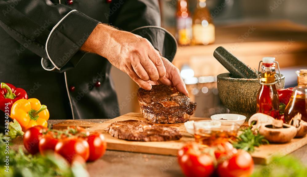 Fototapety, obrazy: Chef seasoning a raw steak for grilling