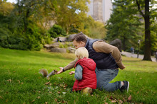 Little Boy With His Father Feeding Squirrel In Central Park, Manhattan, New York. Quality Family Time.