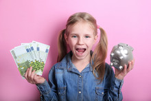 Happy Young Girl With Silver Piggy Bank And Euro Banknotes  On Pink Background. Save Money Concept.
