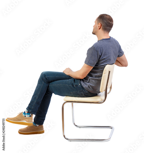 Obraz Side view of a man sitting on a chair. - fototapety do salonu