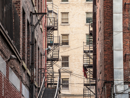 Fire escape stairs and ladder, metal, on a typical North American old brick building from the Old Montreal, Quebec, Canada Fototapet