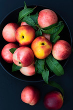 A Bowl Of Ripe Nectarines On A Black Background.