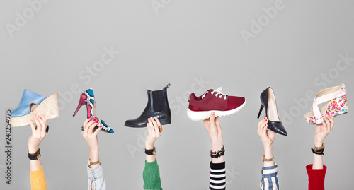 Hands holding different shoes on gray background