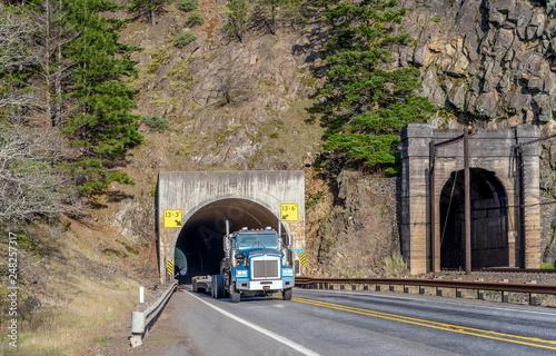 Zdjęcie XXL Duża ciężarówka pół ciężarówki z pustym krokiem naczepą biegnącą przez tunel w skale