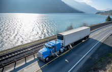 Blue Classic American Bonnet Big Rig Semi Truck Trancporting Cargo In Refrigerated Semi Trailer Moving On The Road Along The River In Columbia River Gorge Area