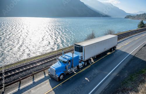 Photo  Blue classic American bonnet big rig semi truck trancporting cargo in refrigerat