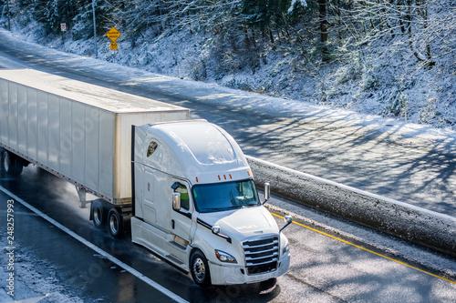 canvas print motiv - vit : Bright white modern big rig semi truck transporting dry van semi trailer running on winter snowy wet road