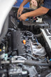 Car service by an auto mechanic in garage, fixing a car battery with wrench, also checking some parts of the engine showing by selective focus.