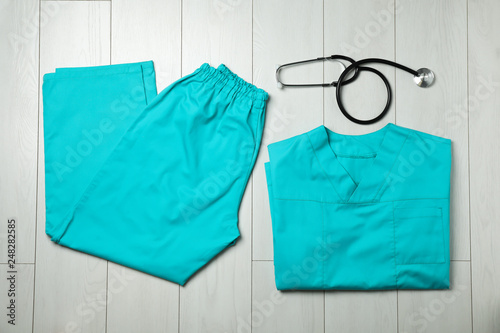 Fotografie, Tablou Clean scrubs and stethoscope on wooden background, top view