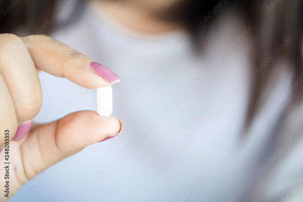 Fototapety, obrazy: closeup woman hand holding one antibiotic pill