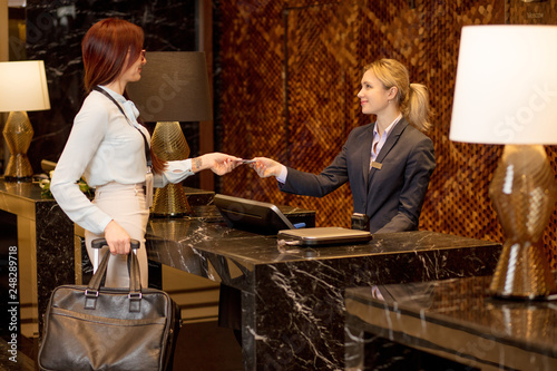 Female business tourist with suitcase and blank white badge arriving to hotel, g Fototapeta